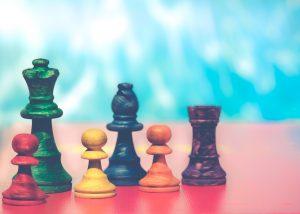 Piezas de ajedrez, reina, alfil torre y tres peones de diferentes colores