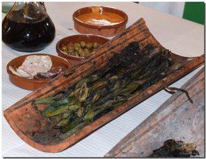 calçots en una teja con cuencos de olivas, butifarra y salsa romesco