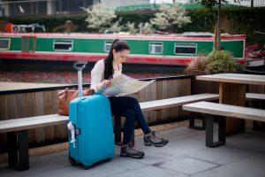Joven sentada en un banco junto a una maleta azul
