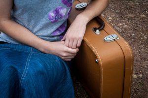 Joven apoyada en una maleta