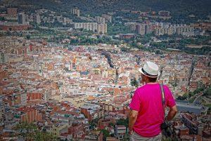 hombre con camiseta rosa mirando la ciudad de Barcelona