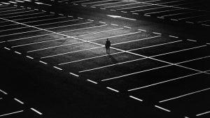 parking de noche con un hombre paseando entre las líneas del parking