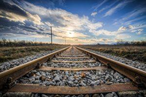 foto de cerca de raíles de tren en una vía donde se ve un atardecer