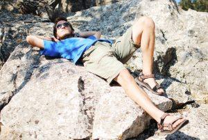 Hombre estirado encima de una roca