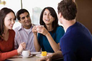 grupo de dos chicas y dos chicos hablando con un café