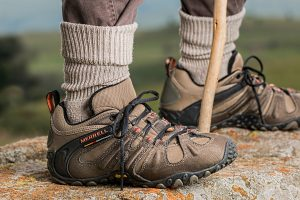 Hombre subido a una roca y con captura de cerca en las botas de montaña
