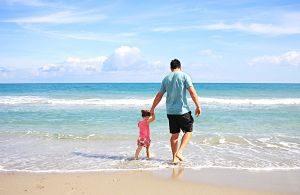 Padre e hija jugando en la orilla de la playa