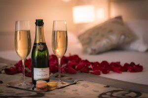 Champagne y pétalos de rosa en la cama