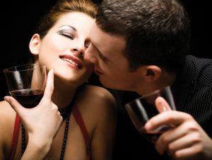 Novios dándose un beso y bebiendo vino