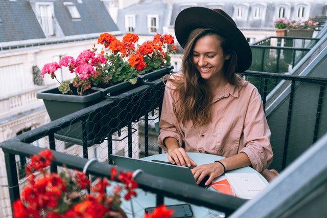chica con sombrero sonriendo en un balcon lleno de macetas con flores
