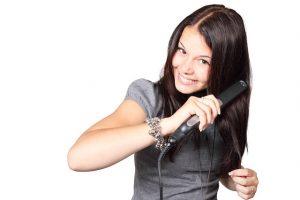mujer morena planchandose el pelo con una plancha de pelo