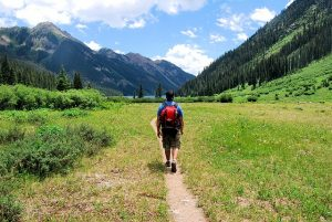 walking with a backpack on a dirt path in a field between mountains