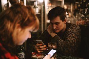 pareja sentados en una mesa mirando sus respectivos móviles