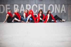 6 chicas sentadas en el suelo con una boa de fiesta de color rojo