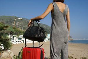 Mujer con bolso y una maleta mirando a la playa