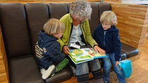 Mujer mayor leyendo a dos niños