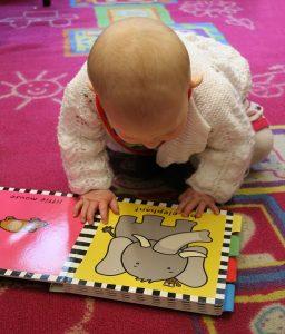 Bebé mirando un libro con un elefante dibujado