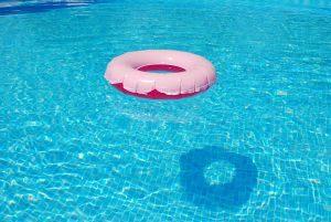 Flotador rosa en la superfície de una piscina