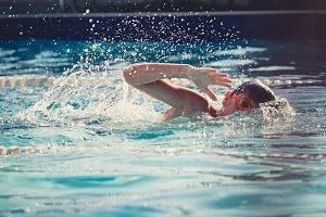 Niño nadando en una piscina descubierta