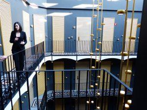imagen de hotel con varias puertas y una mujer hablando