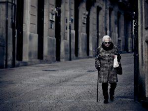 señora con bastón paseando por las calles de Barcelona