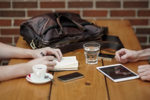 friends-sitting-in-cafe-writing-in-notebook-with-digital-tablet-and-coffee-cup