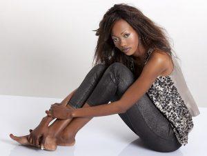 Modelo africana sentada en el suelo mirando cámara