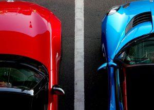 Dos coches uno rojo y otro azul separados por una línea de parquing
