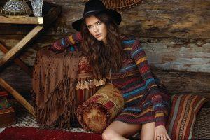modelo posando con sombrero sentado en un sofá rural