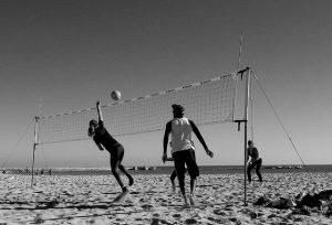 dos personas juegan a voley en la playa
