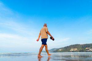 señor mayor paseando descalzo por la playa
