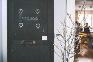 """puerta en un piso con el cartel de """"Bonjour"""" con una flor al lado"""