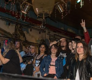 Muchedumbre dentro de un bar mirando a un escenario