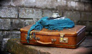 Maleta antigua con una cámara y un foulard encima