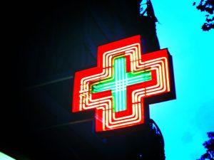 cartel de neón en forma de cruz de la farmacia