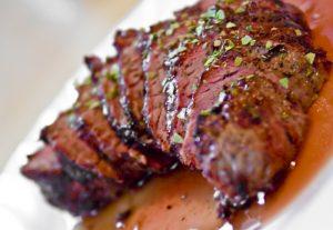 Carne a la brasa cortada con su jugo en el plato