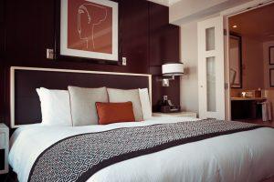 Habitación de hotel con tonos blancos y naranjas.