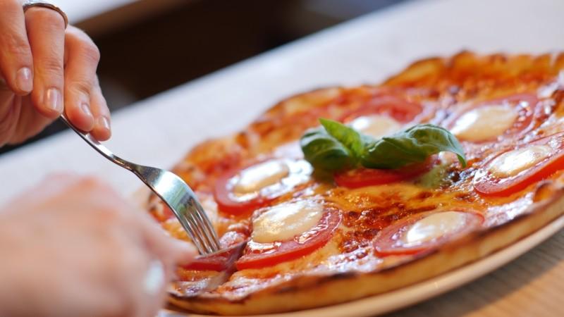 Imagen de una persona cortando una pizza