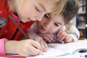 dos niñas mirando una libreta