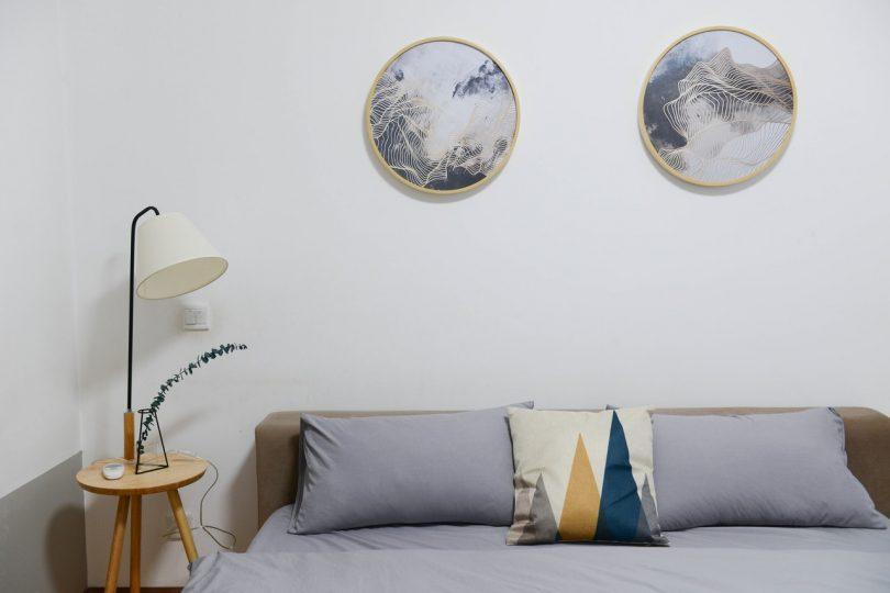 mesita de madera con una lampara encima al lado de una cama gris y dos cuadros redondos en el cabecero