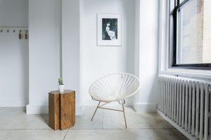 Habitación blanca con silla y mesa auxiliar