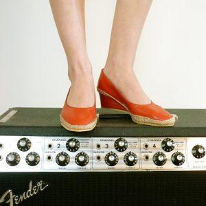 Dos pies con zapatillas rojas.