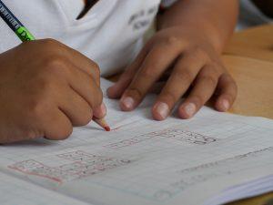 niño escribiendo en su pupitre