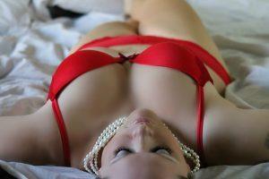 Mujer acostada en la cama con ropa interior roja.
