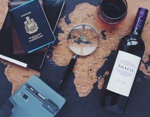 Mesa con un pasaporte, cámara fotográfica. una lupa, un mapa mundi y una botella de vino tinto.