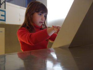 Niña en un museo tocando una pantalla con los dedos.