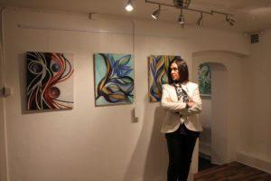Mujer en pose al lado de cuadros de arte.