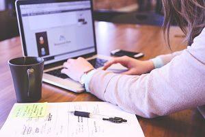 Imagen de una joven escribiendo en el ordenador