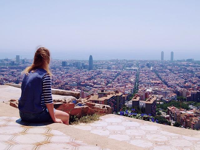 Chica sentada mirando panorámica de Barcelona