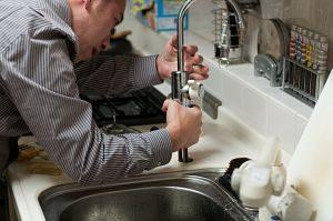Imagen de un fontanero arreglando un grifo